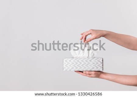 Delicate female hands pulling a tissue out of a gray tissue box. Royalty-Free Stock Photo #1330426586