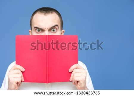 Serious guy, man is shocked after reading the book, close up, background, copy space, for advertising, slogan, front view, blue background