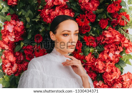 Close up shoot of a beautiful caucassian female model with artificial flower background.Beauty and fashion shoot. #1330434371