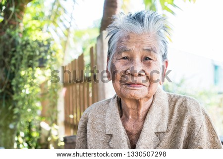 Enjoy Happy Asian old woman / grandmother smiling with her sitting alone with smooth expression / wrinkled and freckled skin at home backyard garden Older people for health insurance concept #1330507298