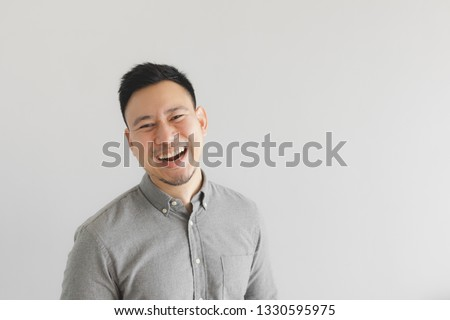 Happy and laughing face of ordinary Asian man in grey shirt. Concept of charming laugh. #1330595975