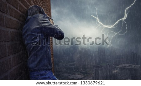 Photo Editor of a man taking a picture of the rain and lightning,Bangkok/Thailand-March 1,2019.