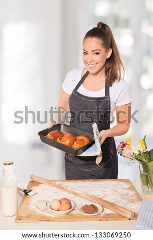 Baking woman showing a tray of cookies fresh out of the oven #133069250