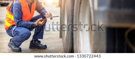Preforming a pre-trip inspection on a truck,Concept preventive maintenance truck checklist,Truck driver holding clipboard with checking of truck. #1330722443