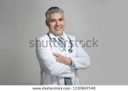Mature doctor on grey background #1330869548