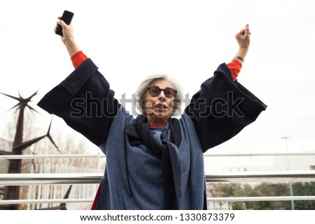 Excited senior lady with smartphone celebrating success. Grey haired mature woman in sunglasses and overcoat throwing hands in air and enjoying win. Success gesture concept #1330873379