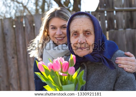 Young woman giving a bouquet of pink tulips to her elderly grandmother  on Women's day, 8th of March. Love, care, gift, togetherness #1330921181