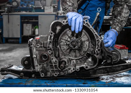 A close-up of a young man repairman in a working uniform of cars is repairing an automatic gearbox of a used car in an auto repair shop. The concept of car repair and car repair shop #1330931054