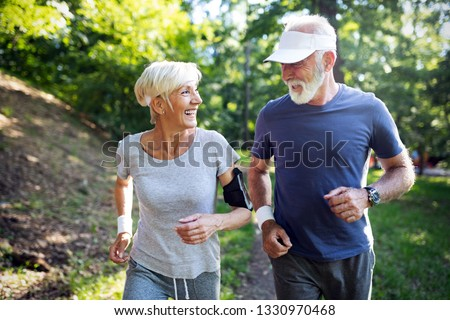 Happy fit senior couple exercising in park #1330970468