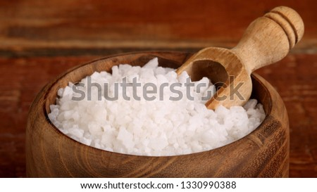 Salt or sea salt in a wooden bowl on a aged wooden table background. #1330990388