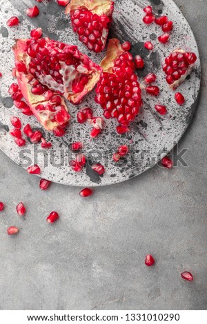 Pieces of ripe pomegranate on grey table #1331010290
