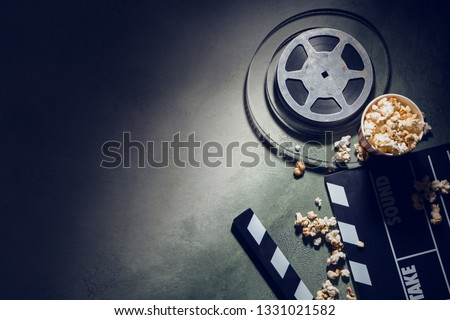 Composition with cinema clapperboard, film reel and popcorn on dark background