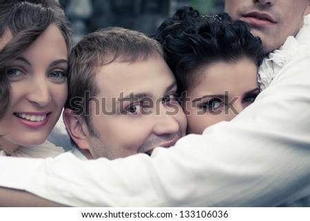 Emotive portrait of four smiling close friends - street actors. Troop at repetition. Close up. Outdoor shot #133106036
