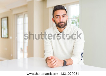 Handsome hispanic man wearing casual white sweater at home Relaxed with serious expression on face. Simple and natural looking at the camera. #1331072081