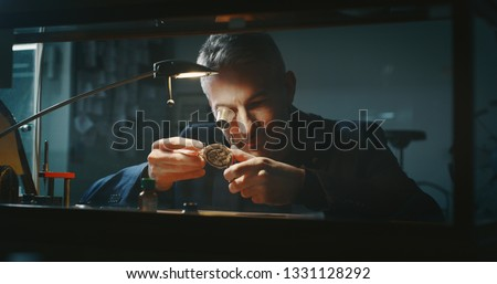 Portrait close up of a professional watchmaker repairer working on an old vintage pocket watch in a workshop.  #1331128292