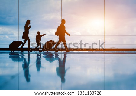 Family at airport travelling with young child and luggage walking to departure gate, girl pointing at airplanes through window, silhouette of people, abstract international air travel concept #1331133728