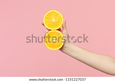 Close up cropped photo of female hold in hand two fresh ripe halfs orange fruit isolated on pink pastel wall background. Copy space advertising mock up. People vivid lifestyle, relax vacation concept