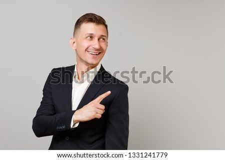 Smiling young business man in classic black suit, shirt looking, pointing index finger aside isolated on grey wall background in studio. Achievement career wealth business concept. Mock up copy space #1331241779