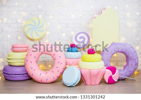 children party background - set of huge artificial sweets and pastry decorations over white brick wall with lights #1331301242