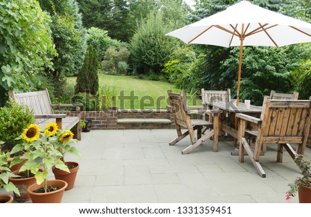 London garden in summer with patio, wooden garden furniture and a parasol or sun umbrella #1331359451