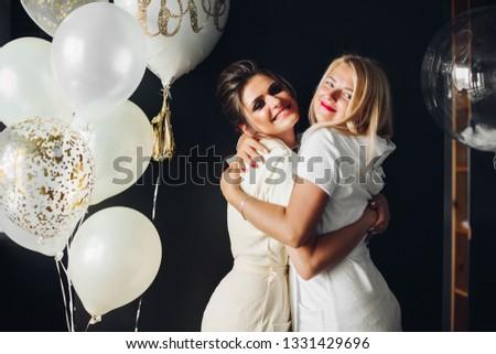 Happy bride hugging with bridesmaid and looking at camera #1331429696