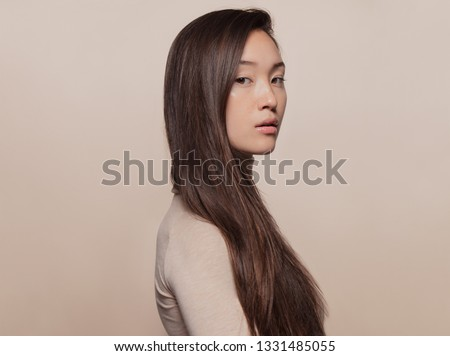 Portrait of beautiful young woman with long brown hair standing against beige background. Asian woman with a long straight hair looking at camera. #1331485055