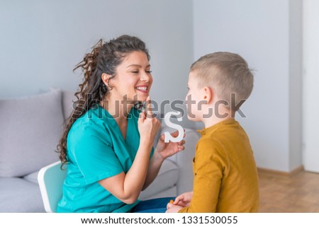 Speech therapist and little patient training articulation. Speech therapist teaches the boys to say the letter S. Shot of a speech therapist during a session with a little boy  #1331530055