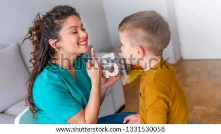 Speech therapist and little patient training articulation. Speech therapist teaches the boys to say the letter S. Shot of a speech therapist during a session with a little boy  #1331530058
