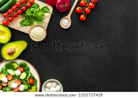 Ingredients for fresh salad. Vegetables, greens, spices, plate of salad on black background top view space for text #1331737439