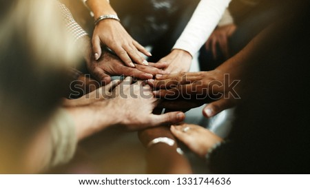 Closeup of diverse people joining their hands Royalty-Free Stock Photo #1331744636