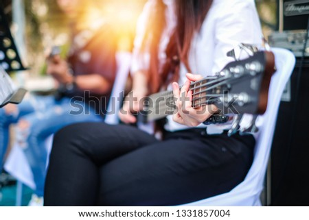 a woman playing a bass in group on the stage.  #1331857004