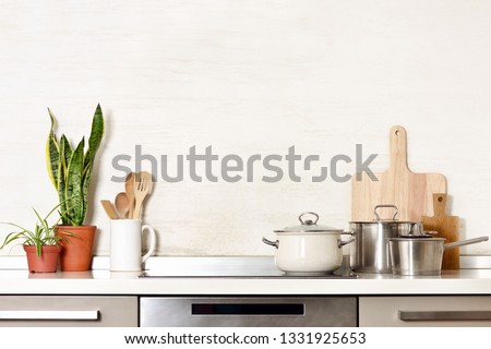Kitchen utensils on a modern home kitchen table top, front view background with blank space for a text #1331925653