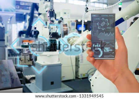 Engineer uses a futuristic transparent smartphone to control robotic arm. Smart industry 4.0 concept. #1331949545