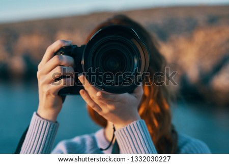 Woman with a camera near a mountain river in nature in the mountains                                #1332030227