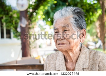 Enjoy Happy Asian old woman / grandmother smiling with her sitting alone with smooth expression / wrinkled and freckled skin at home backyard garden Older people for health insurance concept #1332097496
