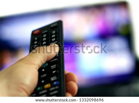 Remote control and screen - watching the favourite TV show #1332098696