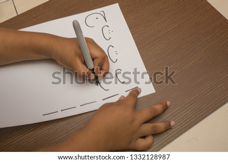 Left handed boy learn to writing Arabic text on white paper