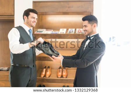 Man in formals selecting best shoes for his marriage in store #1332129368