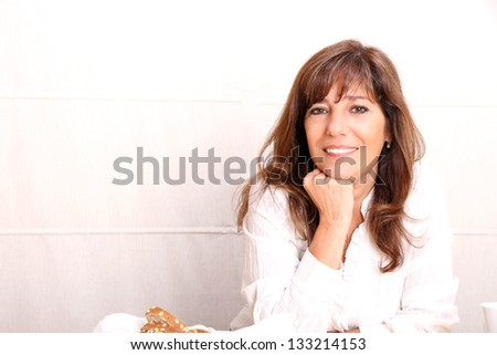Portrait of a beautiful mature woman sitting in the kitchen. #133214153