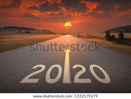 Driving on idyllic open road against the setting sun forward to upcoming 2020 new year. Concept for success and future.