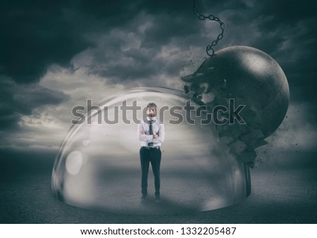 Businessman safely inside a shield dome during a storm that protects him from a wrecking ball. Protection and safety concept #1332205487