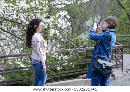 Young woman taking picture of another one standing in front of magnolia flowers in a city park. March 20, 2018. Kiev, Ukraine #1332251741
