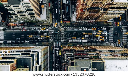 Aerial view of New York downtown building roofs. Bird's eye view from helicopter of cityscape metropolis infrastructure, traffic cars, yellow cabs moving on city streets and crossing district avenues #1332370220