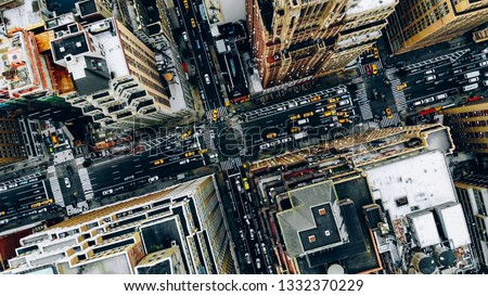 Aerial view of New York downtown building roofs. Bird's eye view from helicopter of cityscape metropolis infrastructure, traffic cars, yellow cabs moving on city streets and crossing district avenues #1332370229