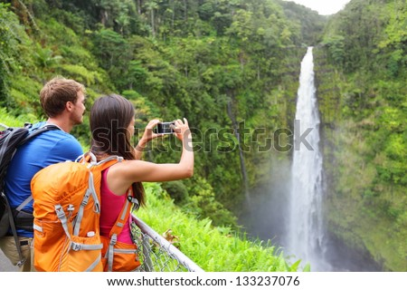 Couple tourists on Hawaii by waterfall. Tourist taking photo pictures of Akaka Falls waterfall on Hawaii, Big Island, USA. Travel tourism concept with multicultural tourist couple.