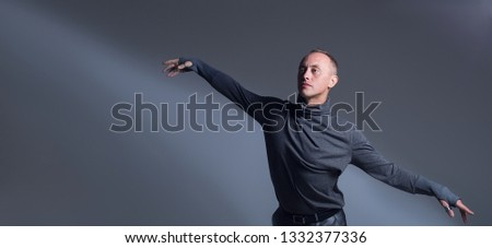 The guy is dancing Contemporary in a gray turtleneck. The man opens his arms like wings and this is underlined by a shadow pattern on a gray background. The ease and grace of dance. #1332377336