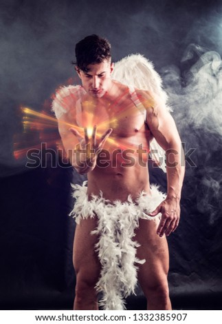 Naked male angel sitting in dark with white feather wings spreading from his back, holding ball of energy in hand. Angelic naked young man standing on dark background #1332385907