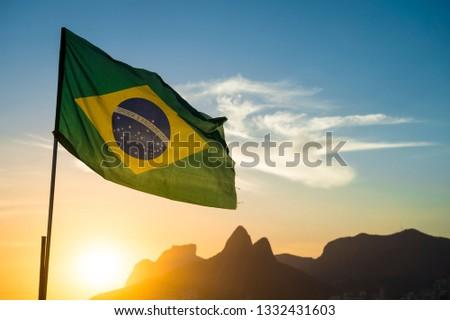 Brazilian flag waving backlit in front of the golden sunset mountain skyline at Ipanema Beach in Rio de Janeiro, Brazil #1332431603