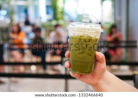 Matcha Whip cheese. Woman hand holding a plastic cup of matcha latte topped with cheese cream. #1332466640