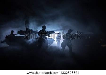 War Concept. Battle scene on war fog sky background, Fighting silhouettes Below Cloudy Skyline at night. Army vehicle with soldiers artwork decoration #1332508391